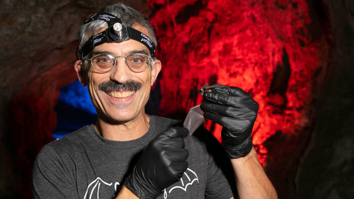 Tomasi poses with a bat inside a cave
