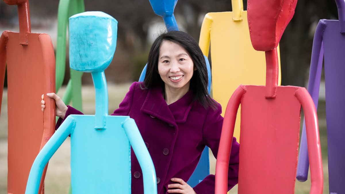 Xiaomin Qiu stands among colorful sculptures of stick figures