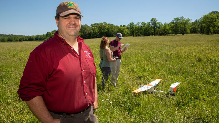Michael Goerndt poses in foreground while others work on drone behind him