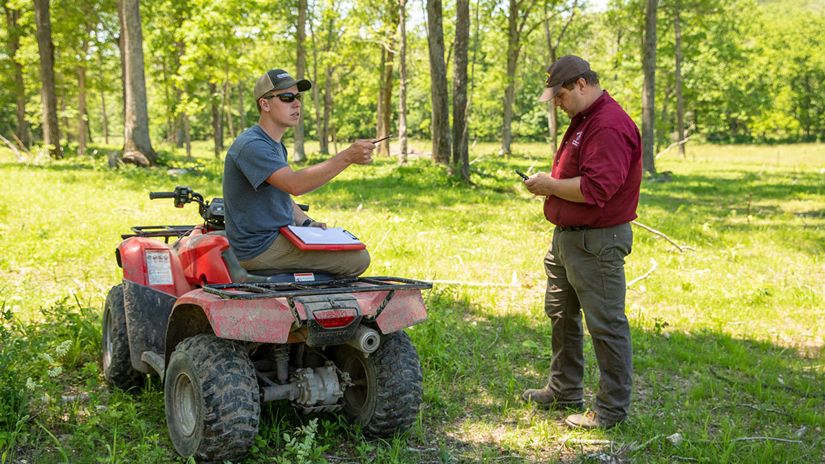 Stewart McCollum sits on four-wheeler talking to Dr. Michael Goerndt
