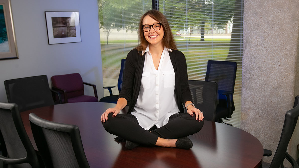 Carrisa Hoelscher sits cross-legged on a conference room table.