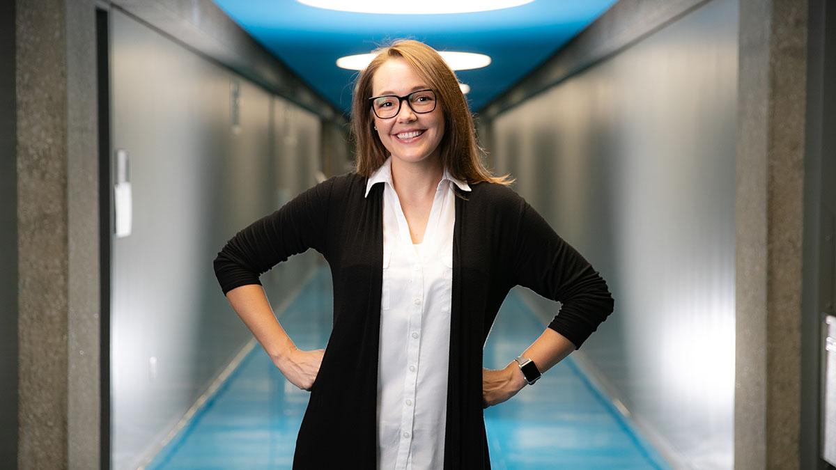 Carrisa Hoelscher stands in blue hallway of Craig