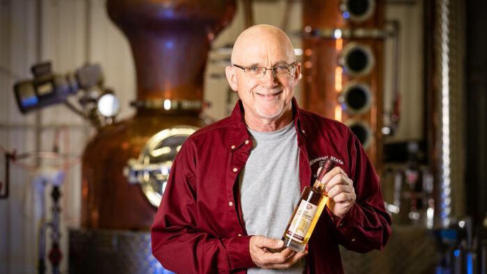 Karl Wilker with award-winning rum in distillery