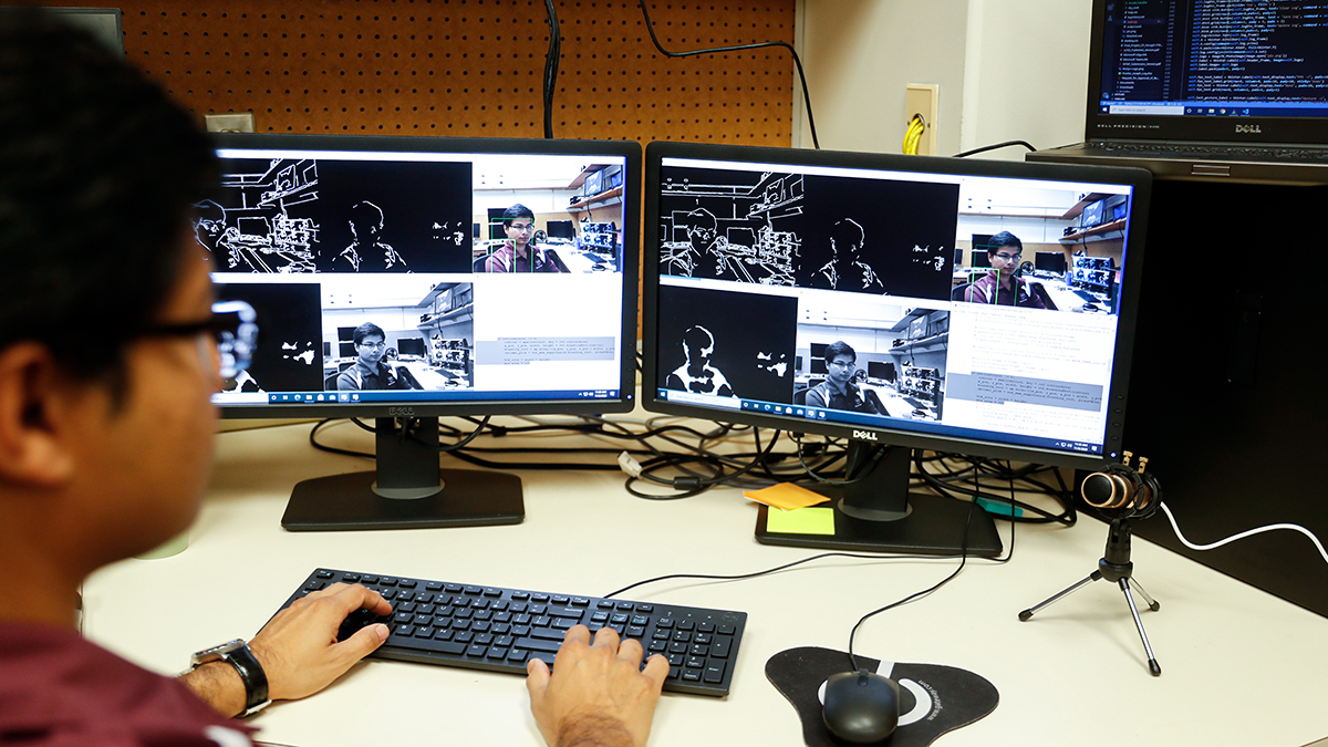 Man works at dual-screen computer with 6 images of himself on the screen.