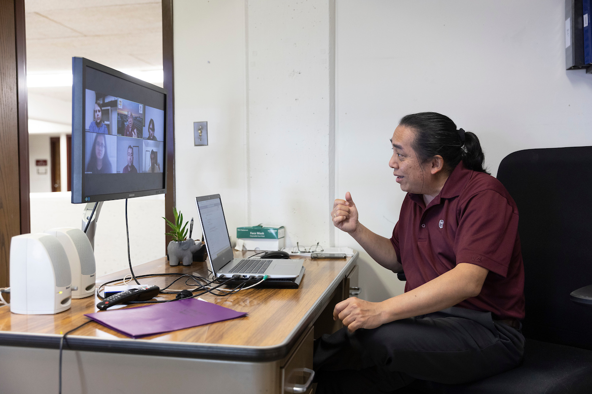 Ridwan Sakidja talks to his students over Zoom at his desk.