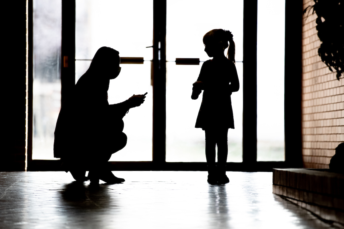Shadow of Megan Boyle squatting to speak with young child by glass doors.