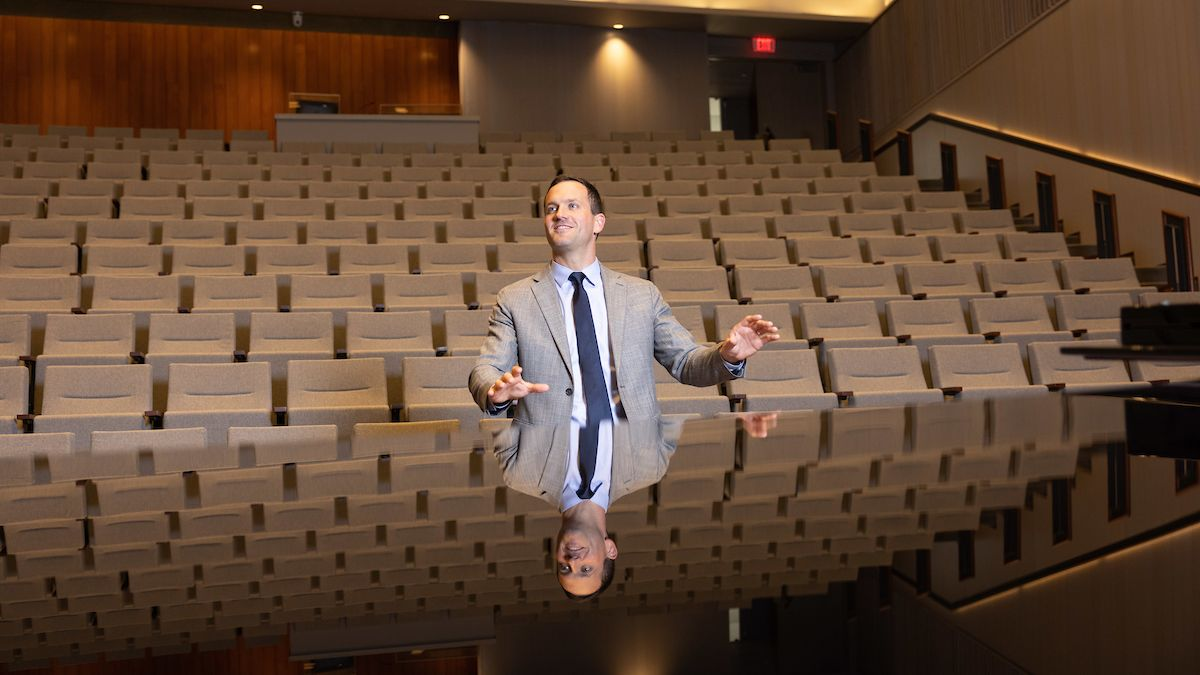 Cameron LaBarr conducts as his reflection shines from the top of the grand piano.