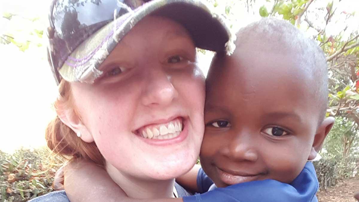 Karlie Beckett and a child in Haiti
