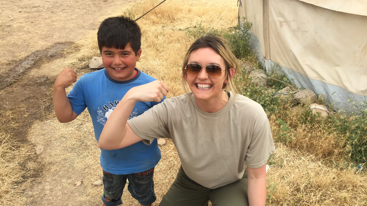 Madeline Hayes with a kid in Mosul
