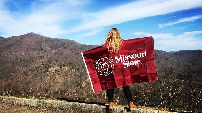 Kenna Sheppard posing with Missouri State University flag in Australia.
