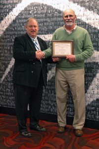 Dr. John Bourhis being awarded by Gary Rader