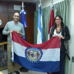 This photo is taken with Mayor Martino in his office in Rio Tercero, Argentina with Professor Mariana Gonzalez,  they are holding a Missouri flag flown over the Missouri State Capitol building and given to Professor Gonzalez by Representative Kevin Austin last week in Jefferson City.