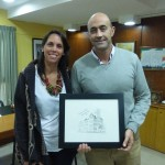 This photo is Professor Mariana Gonzalez in the office of Mayor Martino in Rio Tercero, Argentina They are holding an engraving of the old Springfield City Hall,  The picture was given by Mayor Robert Stephens of Springfield, Missouri to Mayor Martino.