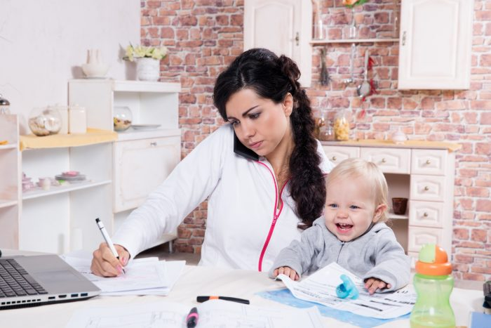 Mother with baby in the kitchen working with documents and speaks by phone