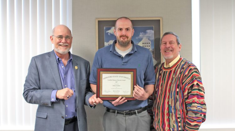 Dr. Gary Rader and Dean Victor Matthews present Ethan Amidon with a Certified Distance Educator Award.