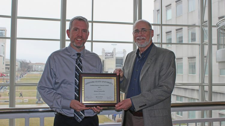 Mike Suttmoeller receives his Certified Distance Educator Award from Dr. Gary Rader