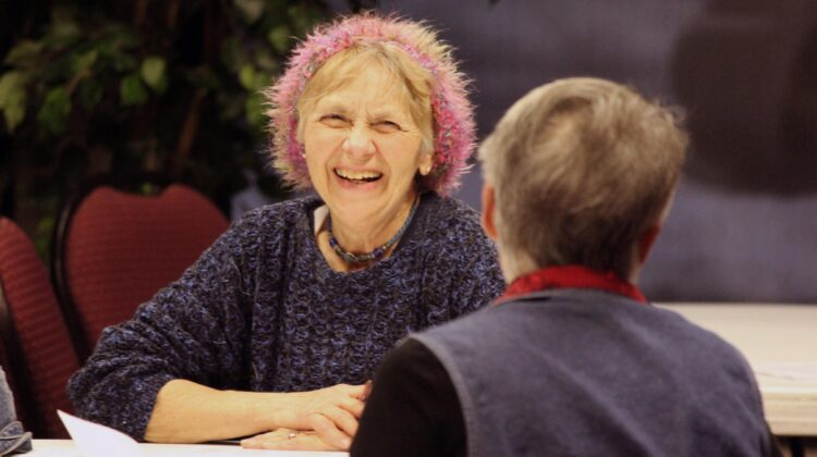 Smiling senior citizen in a pink hat chats across the table with another woman at MSU 62's registration event.