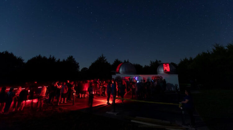 A nighttime view of Baker Observatory as a line forms outside of the viewing stations.