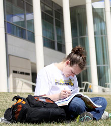 Student studying outside library