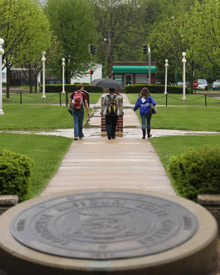 Students walking past the seal
