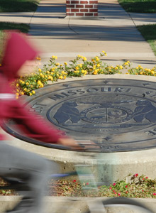 Student riding a bike by the University seal