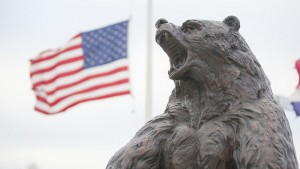 The Plaster Stadium Bear Statue with the U.S. Flag at half-staff in the background.