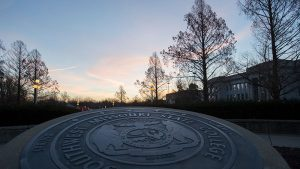 University seal at sunrise in front of Carrington Hall