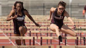 Women running hurdles