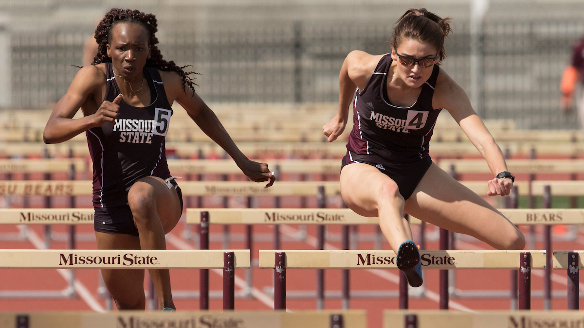 Women running hurdles
