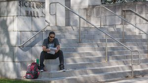 Student sits on steps of Siceluff Hall