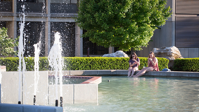 Students sit with feet in fountain