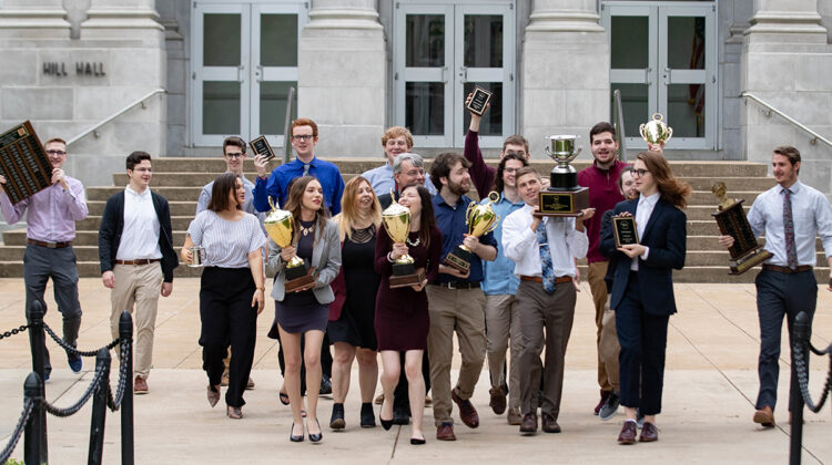 Debate team with awards in front of Hill Hall