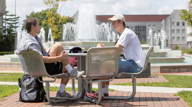 Students sit by fountain