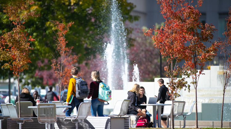Students walk past fountain on fall day