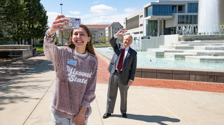 Student takes selfie with Clif (with social distance) in front of fountain