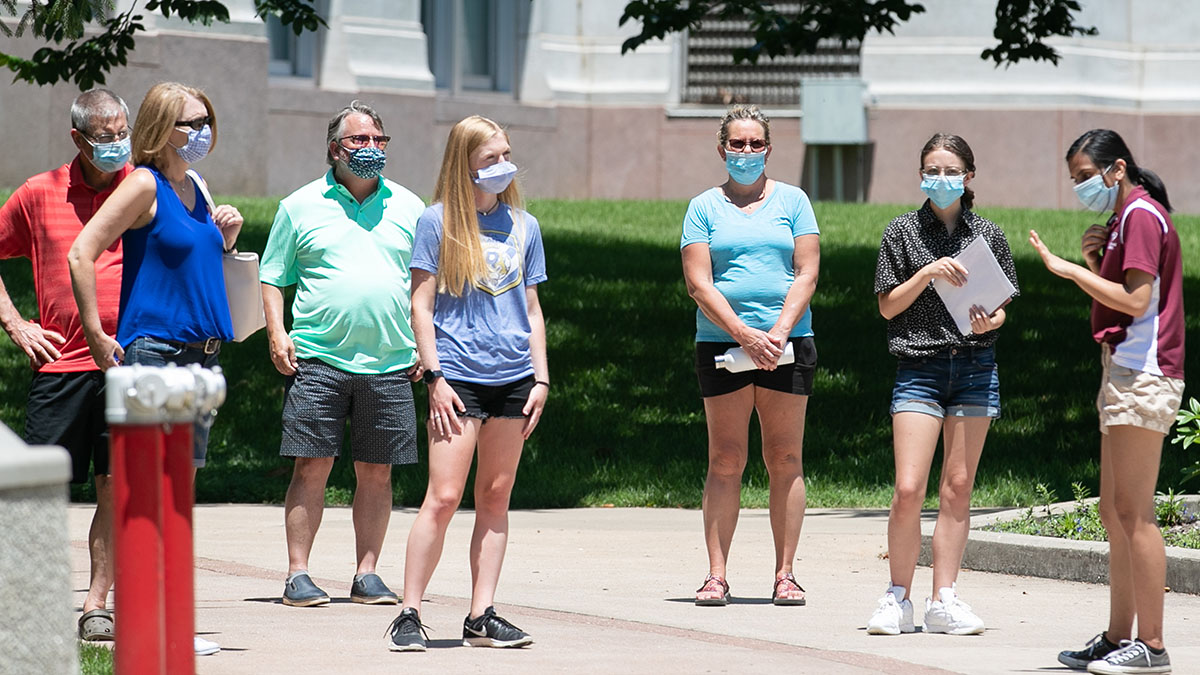 Prospective students and parents tour campus wearing masks.