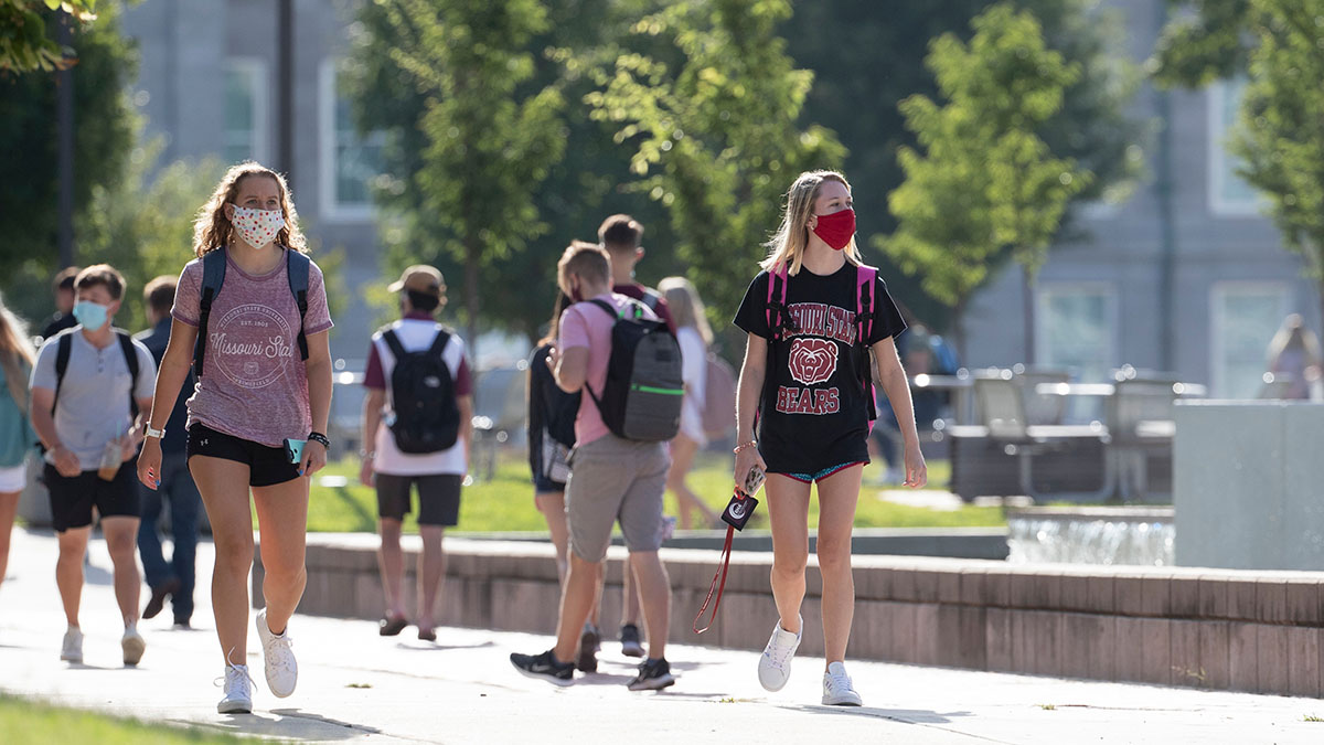 Masked students walk across campus