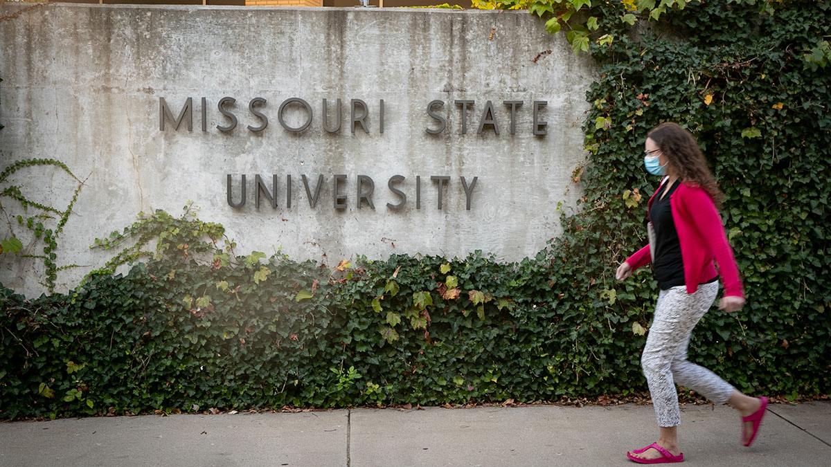 Female student walks past legacy wall.