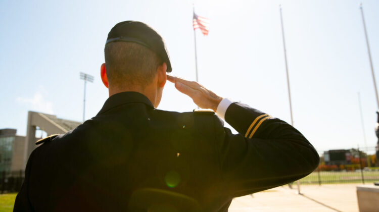 Vet in uniform saluting, seen from back.