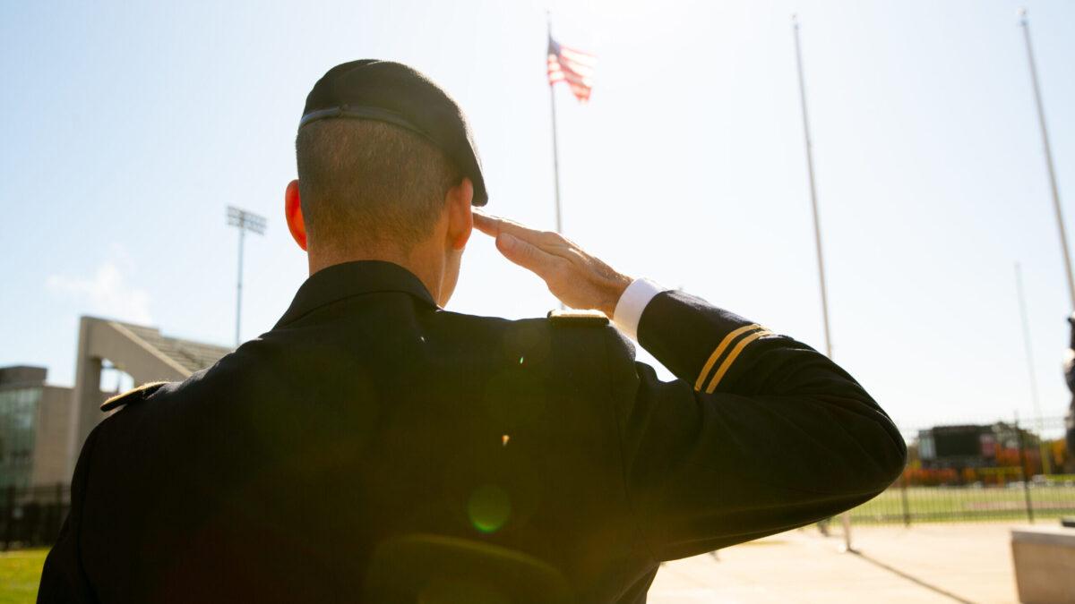 Vet in uniform saluting, seen from back.