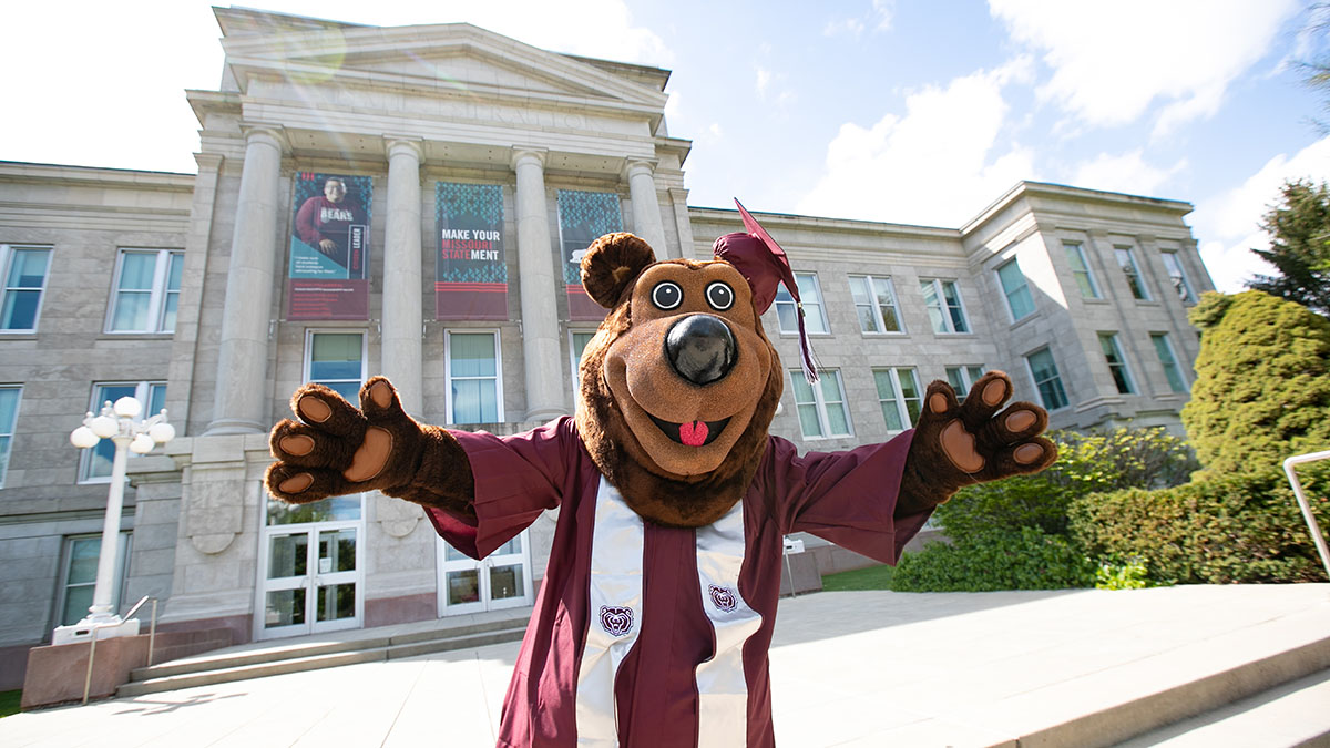 Boomer poses in cap and gown in front of Carrington
