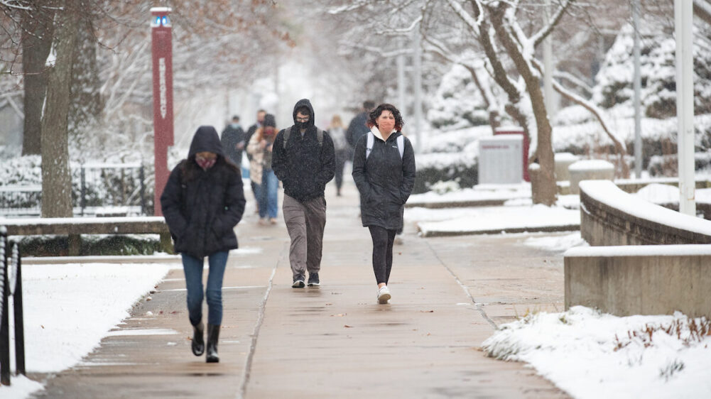 Masked students on snowy walkway.