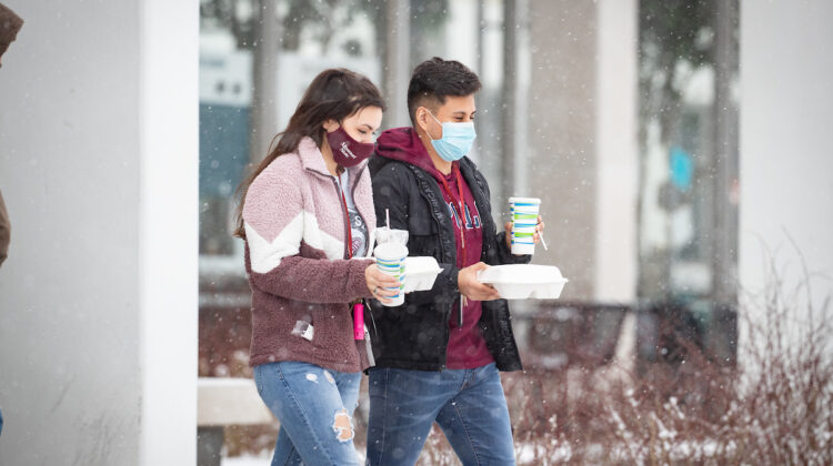Two masked students carry food out of PSU in snow.