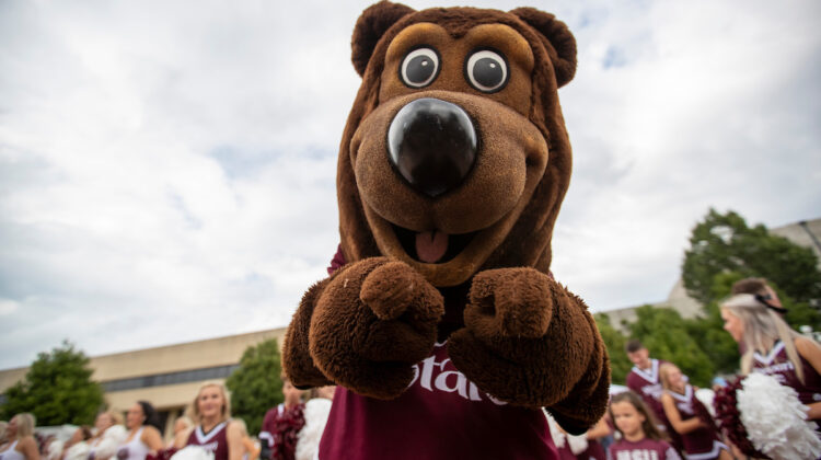 Boomer points at the camera with cheerleaders in background.