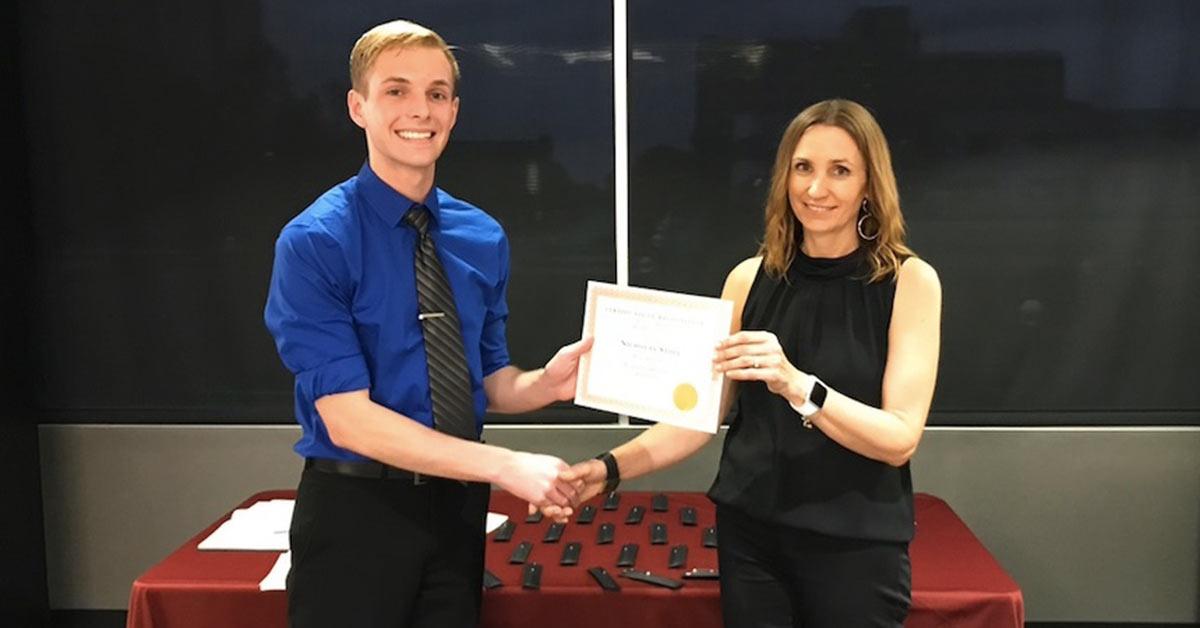 Nicholas Stoll receiving scholarship award from professor.