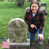 Photo of Katherine Pollock by the gravestone of Susan B. Anthony
