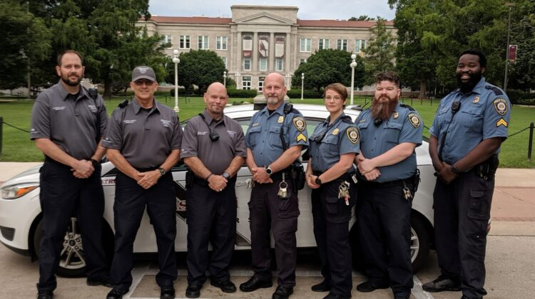 This photo shows the four off-going Campus Safety personnel with the original police style uniform next to the three on-coming personnel with the new polo style uniform.