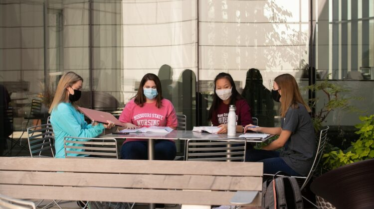Four Missouri State nursing students wear protective face coverings and work together on a project.