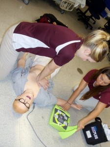 Kristin Tivener (left) provides chest compressions to a high-fidelity mannequin with assistance with the AED from AT student Abby Ekert (2013 alumni).