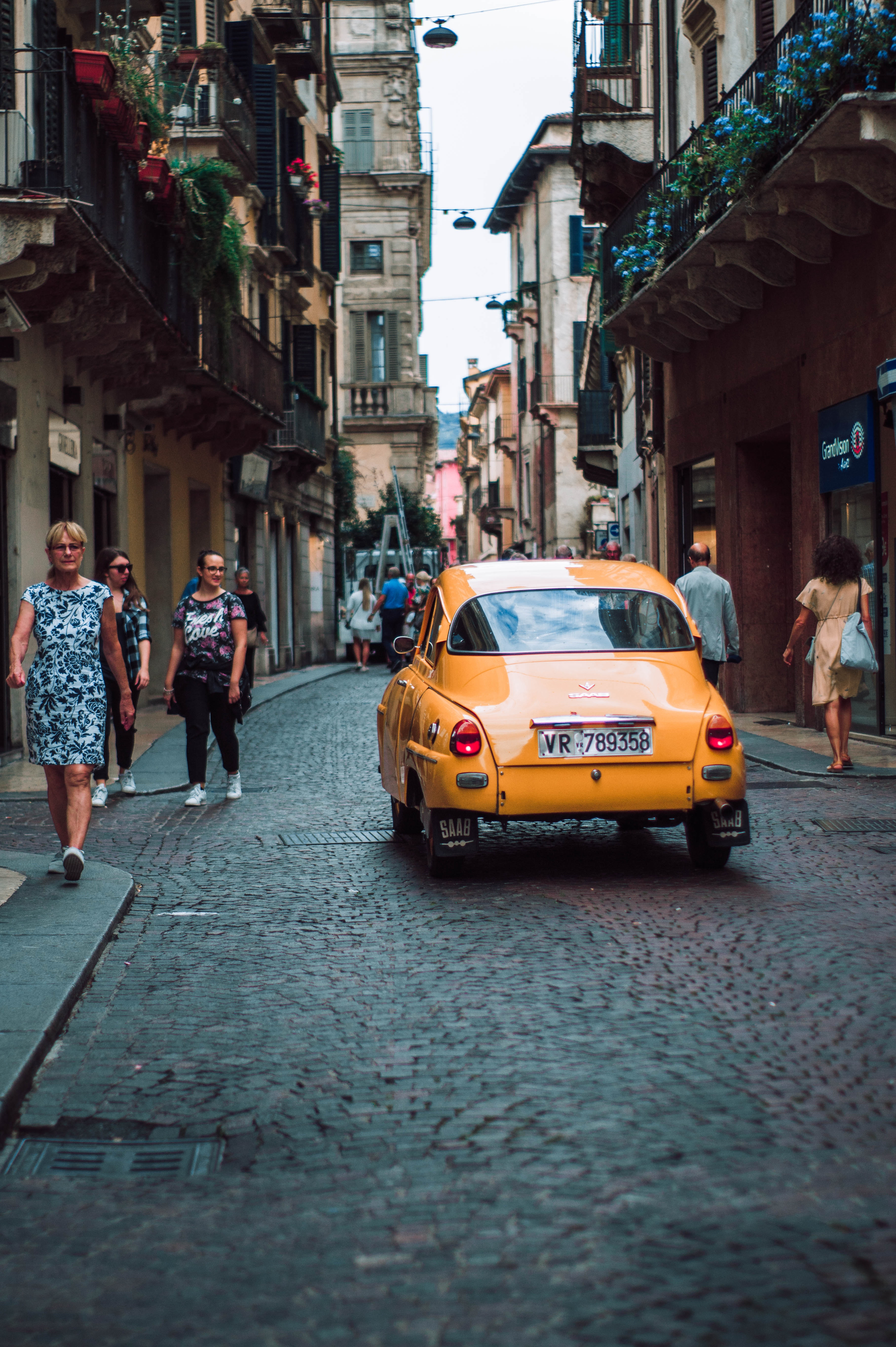 Car driving down cobble stone street in Italy.